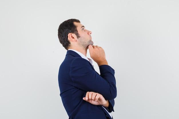 Macho joven apoyando la barbilla en la mano en camisa, chaqueta y mirando pensativo