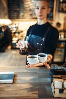 Macho joven barista sostiene dos tazas de café recién hecho