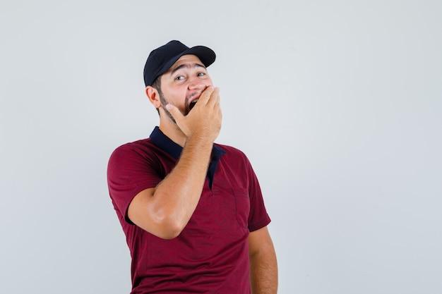 Macho joven bostezando con la mano en la boca en camiseta roja, gorra negra y aspecto cansado. vista frontal.