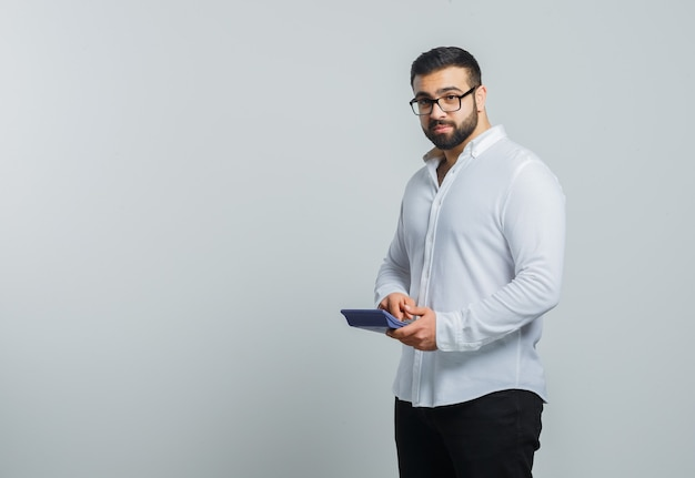 Macho joven con calculadora en camisa blanca, pantalones y mirando pensativo