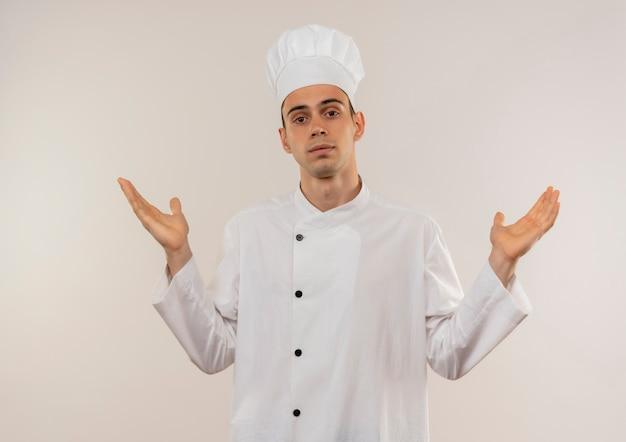 Macho joven cocinero vistiendo uniforme de chef extiende las manos sobre la pared blanca aislada con espacio de copia