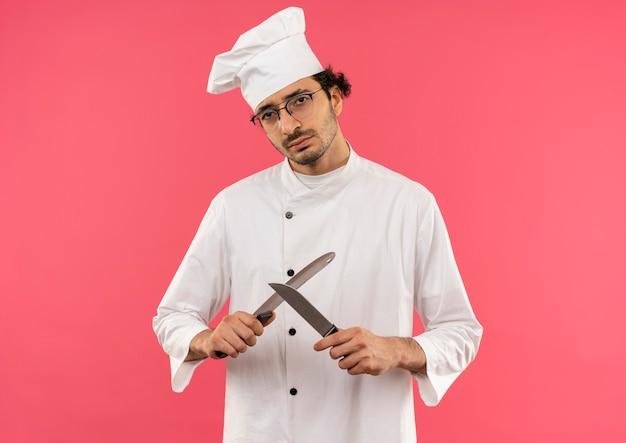 Macho joven cocinero vistiendo uniforme de chef y gafas formas cuchillo con cuchilla