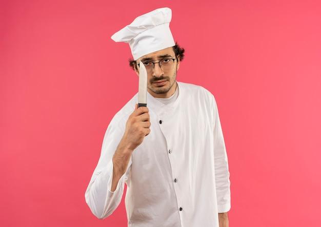 Macho joven cocinero vistiendo uniforme de chef y gafas sosteniendo un cuchillo