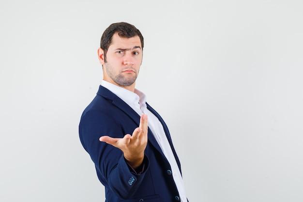 Macho joven estirando la mano en gesto de perplejidad en camisa y chaqueta