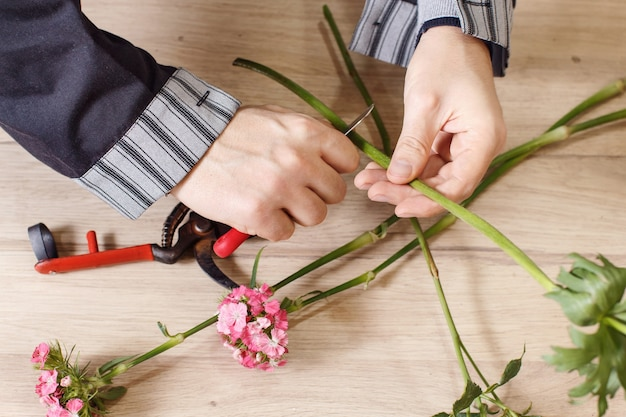 Macho joven floreria cortando flores en la florería, cerrar