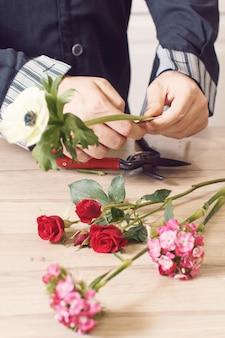 Macho joven floreria cortando flores en la florería