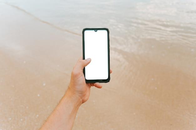 Macho joven mano agarrando un teléfono con copia espacio en vertical con la arena y el mar de la playa como fondo