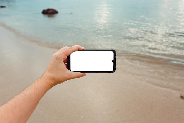 Macho joven mano agarrando un teléfono con espacio de copia en horizontal con la arena y el mar de la playa como fondo