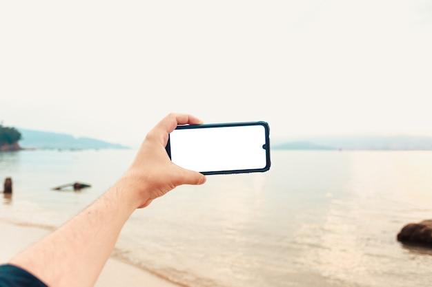 Macho joven mano agarrando un teléfono con espacio de copia en horizontal con el océano como fondo