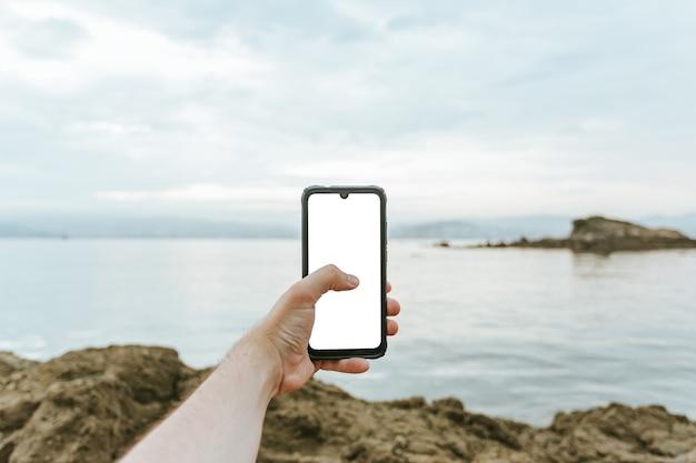 Macho joven mano agarrando un teléfono con espacio de copia y el mar como fondo