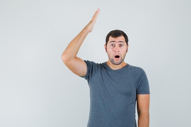 Macho joven manteniendo el brazo levantado en camiseta gris y mirando sorprendido