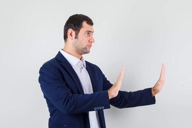 Macho joven manteniendo las manos para defenderse en camisa, chaqueta y mirando tranquilo
