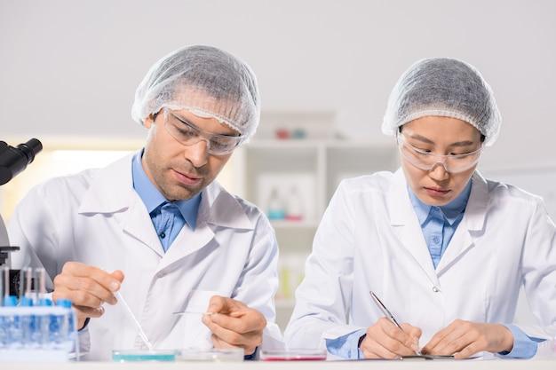 Macho joven químico estudiando muestras de sustancias químicas mientras su asistente cerca tomando notas durante la investigación científica en el laboratorio