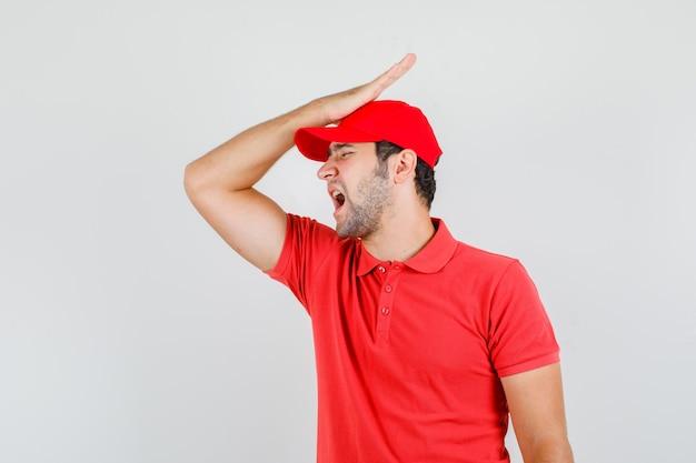Macho joven sosteniendo la mano en la cabeza en camiseta roja