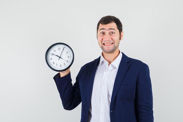Macho joven sosteniendo el reloj de pared en camisa y chaqueta y mirando alegre