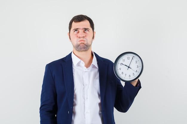Macho joven sosteniendo el reloj de pared en camisa y chaqueta y mirando pensativo