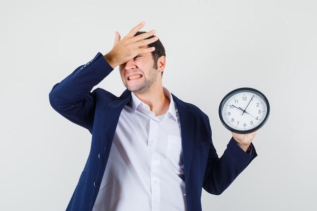 Macho joven sosteniendo el reloj de pared con la mano en la frente en camisa y chaqueta y mirando olvidadizo