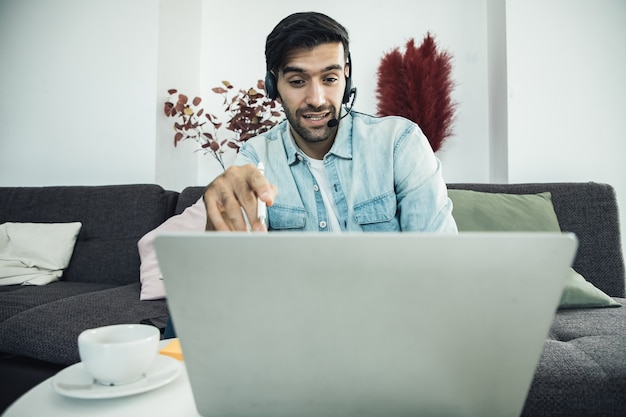 Macho joven en su computadora portátil al personal del operador del centro de llamadas hablando con los clientes a través de auriculares