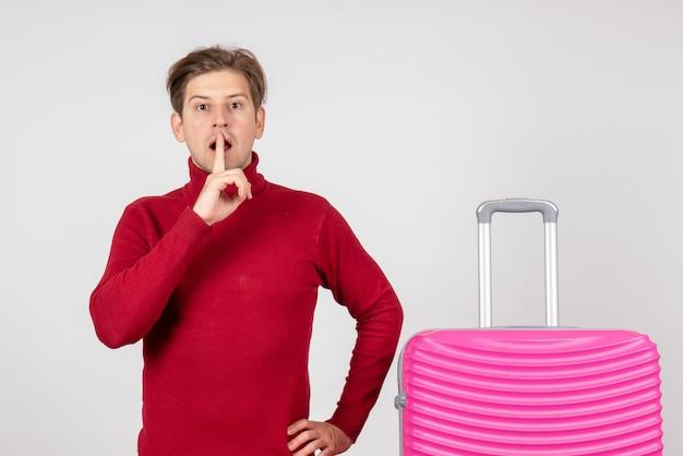 Macho joven de vista frontal con bolsa rosa sobre fondo blanco. Foto gratis