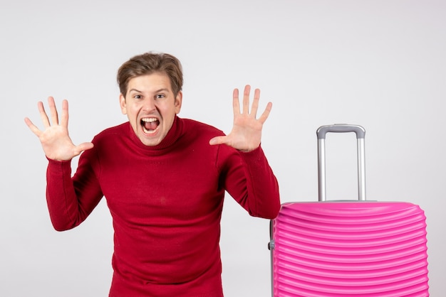 Macho joven de vista frontal con bolsa rosa sobre fondo blanco.
