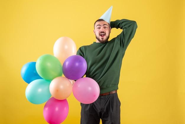 Macho joven de vista frontal con globos de colores sobre fondo amarillo