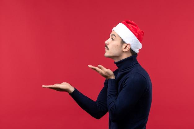 Macho joven de vista frontal con gorra roja de vacaciones sobre fondo rojo.