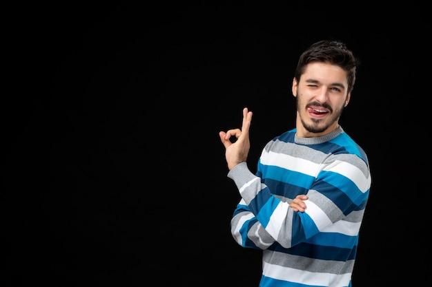Macho joven de vista frontal en jersey de rayas azul haciendo gesto bien