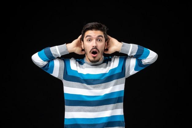 Macho joven de vista frontal en jersey de rayas azules en la pared negra