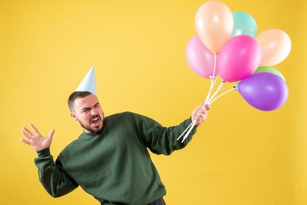 Macho joven de vista frontal sosteniendo globos de colores sobre un fondo amarillo