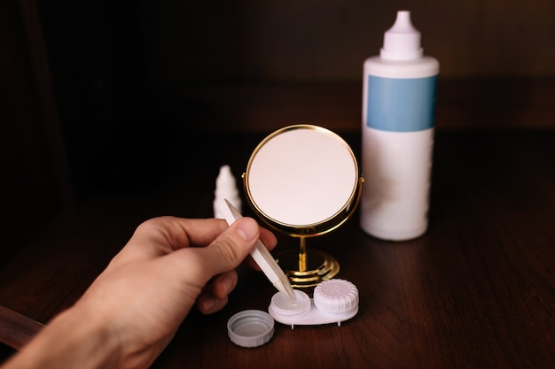Macho mano pinzas en los dedos y tomar lentes de contacto. botella de solución
