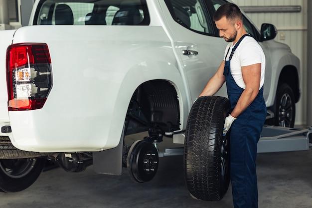 Macho mecánico cambiando las ruedas del coche