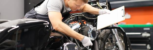 Macho mecánico diagnostica piezas de motocicleta en el centro de servicio