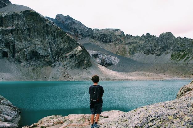 Macho con una mochila de pie en un acantilado disfrutando de la vista del mar cerca de una montaña