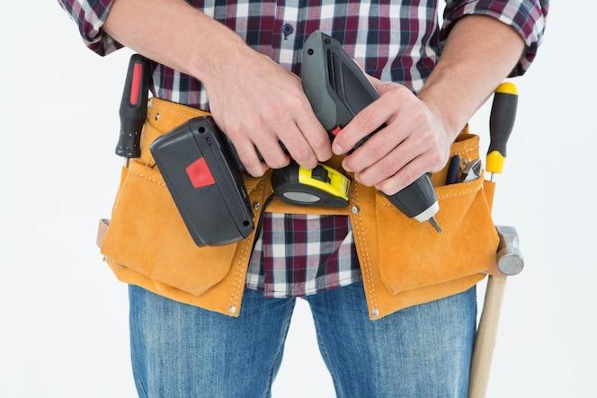 Macho reparador sosteniendo la máquina de taladro