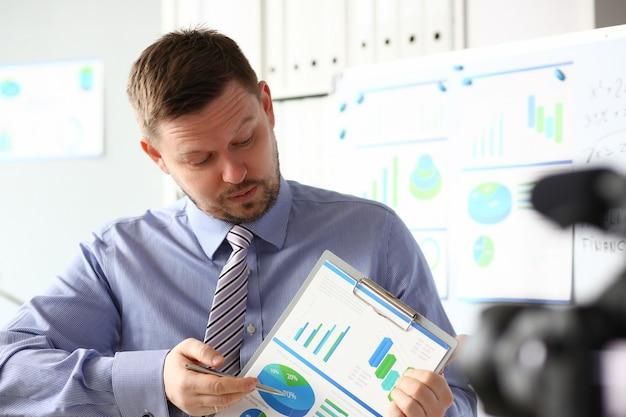 Macho en traje y corbata muestran estadísticas pad gráfico