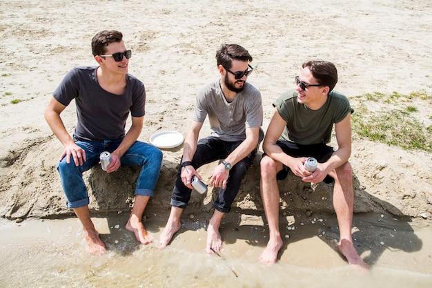 Machos descalzos charlando en la playa de arena