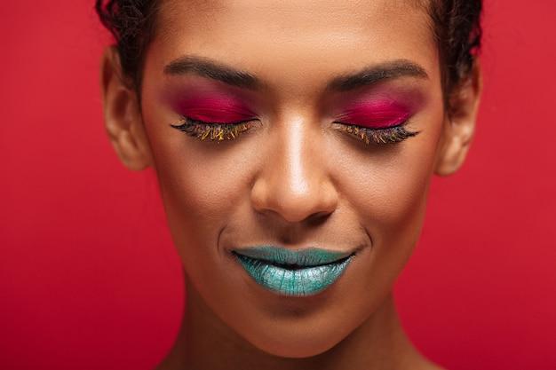 Macro encantadora mujer afroamericana está de moda y de moda vistiendo coloridos cosméticos posando con los ojos cerrados, sobre la pared roja
