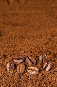 Macro de granos de café sobre fondo café molido