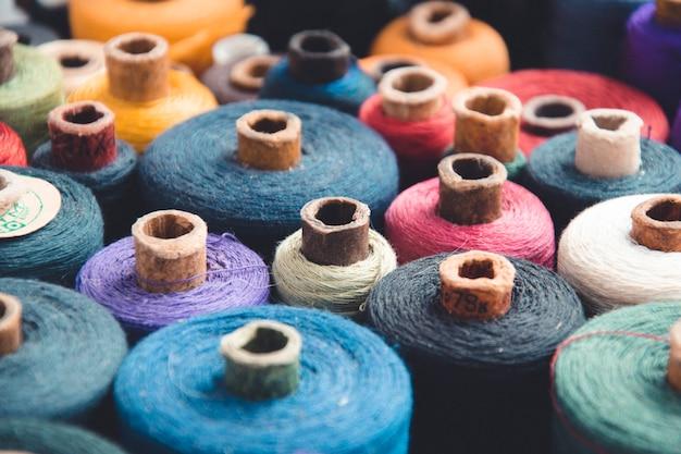 Madejas multicolores y bobinas de hilos. accesorios de costura del taller