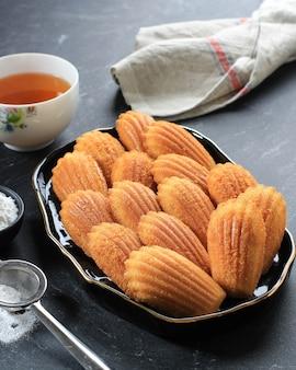 Madeleine, famosa pastelería dulce francesa con azúcar en polvo. sirva en un plato negro