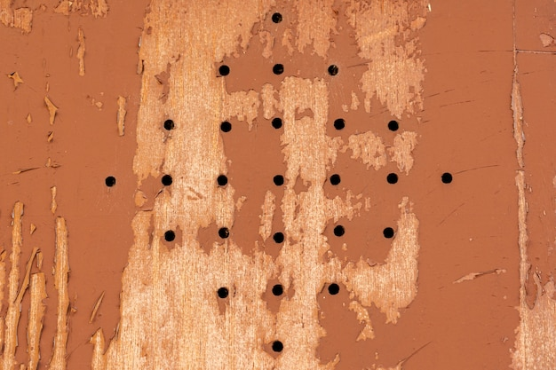 Madera con agujeros y pintura desconchada