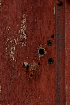 Madera envejecida con agujeros y metal oxidado.