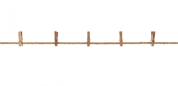 Madera, pinzas viejas colgando de una cuerda. sobre fondo blanco