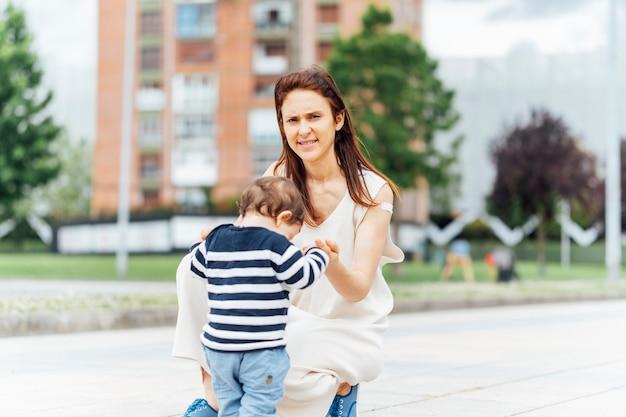 Madre de 37 años con su bebé en la calle enseñándole a caminar