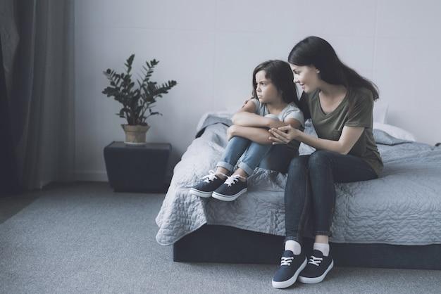 Madre abraza calma hija molesta en dormitorio