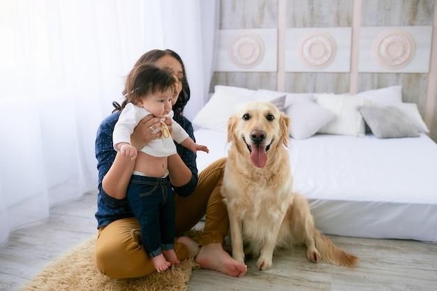 La madre abraza a su hija y se sienta cerca de un perro