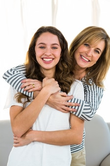 Madre abraza a su hija y sonríe a la cámara.
