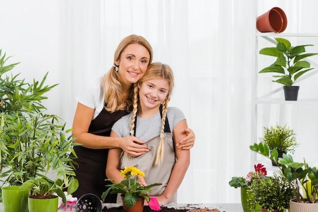 Madre abrazando a hija en invernadero