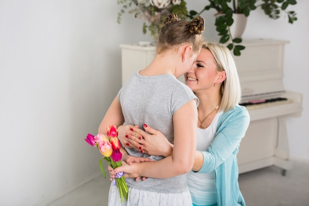 Madre abrazando a hija con ramo escondido