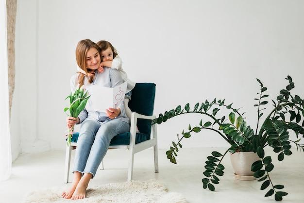 Madre abrazando hija con tarjeta de felicitación